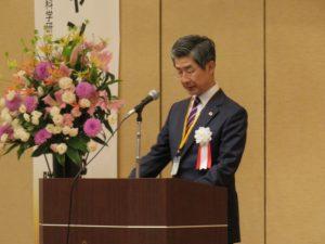 あいさつする鈴木隆一代表幹事